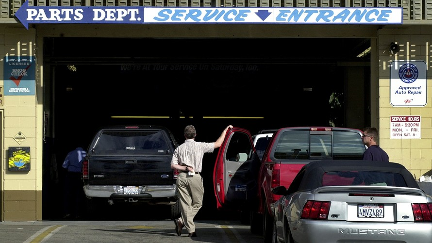 Man standing by car at dealership